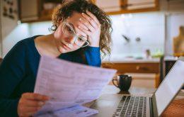 Een vrouw leest haar rekeningen en moet belasting betalen